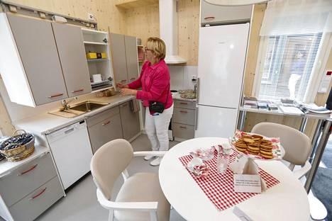 Lapinjärvitalossa keittiökaapiston korkeutta voi kätevästi säädellä. Ominaisuutta esittelee Katri Sibelius.