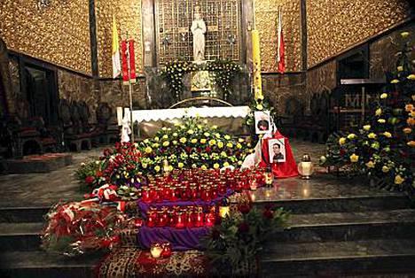 Varsovan sotilaskirkon alttarilla oli esillä kahden turmassa kuolleen papin kuvat.