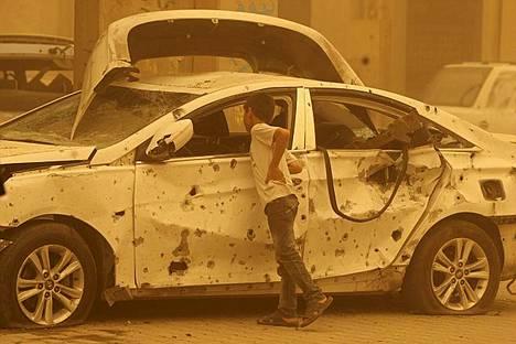 Irakilainen poika tutkii autopommi-iskussa tuhoutunutta autoa Bagdadin Haifa Streetillä. Viranomaisten mukaan pommi-iskujen sarja tappoi ainakin 37 ihmistä ja yli 150 haavoittui eri puolilla Irakia.