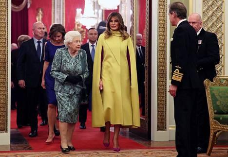 Melania Trump oli sonnustautunut näyttävästi keltaiseen, viittamaiseen leninkiin.