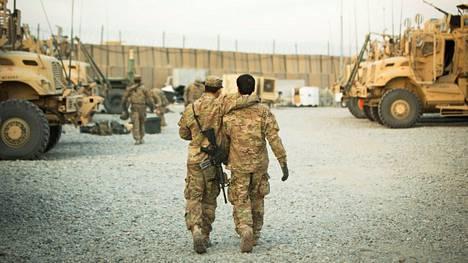 Yhdysvaltalaissotilas kävelee afganistanilaisen tulkin kanssa Gamberin tukikohdassa Afganistanissa joulukuussa 2014.