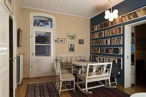 Vaalea kahvipöytä ja penkit ovat saaneet rinnalleen seinään upotetut kirjahyllyt.