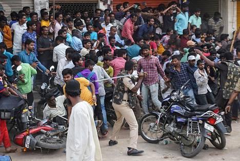 Poliisit yrittivät taltuttaa poliisiaseman piirittäneitä raivostuneita mielenosoittajia patukoidensa avulla Hyderabadissa lauantaina.