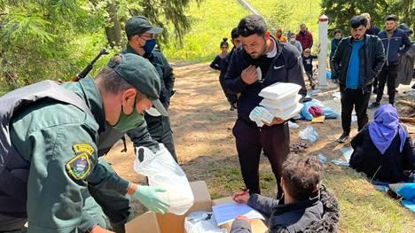 Latvialaiset jakoivat ruokaa siirtolaisille Latvian-Valko-Venäjän rajalla ennen ryhmän katoamista.