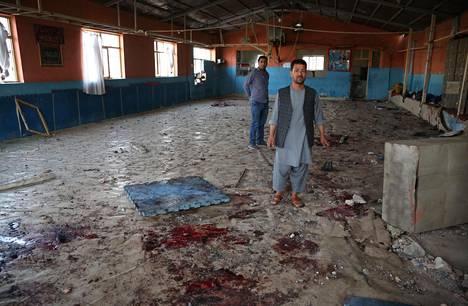 Miehet tutkivat edellisenä päivänä terrori-iskujen kohteeksi joutunutta painisalia torstaina Kabulissa.
