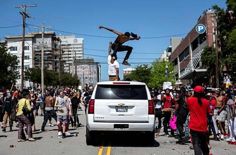 Mellakoihin osallistunut henkilö hyppii auton päällä Columbiassa, Etelä-Carolinassa.