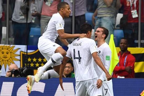Mbappe (vas.) on iskenyt käynnissä olevassa MM-turnauksessa kolme maalia. Kuvassa nuori hyökkääjä juhli Ranskan osumaa puolivälierässä Raphael Varanen ja Antoine Griezmannin kanssa.