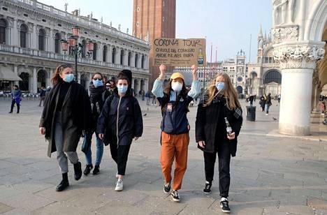 Italian Venetsiassa ohikulkijat käyttävät hengityssuojaimia suojautuakseen maassa leviävältä koronavirukselta.