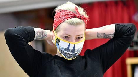 Nainen asettaa itse tehdyn maskin kasvoilleen kuvituskuvassa.
