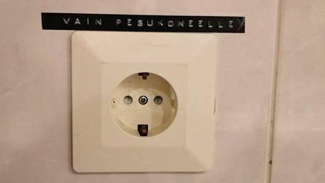 """Kylpyhuoneen pistorasian vieressä lukee teksti """"vain pesukoneelle""""."""