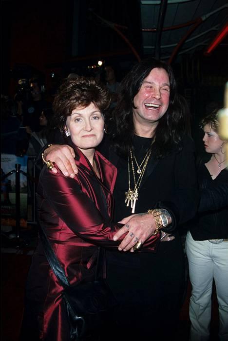 Sharon Osbourne hymyili kameralle melko erinäköisenä vuonna 2000. Vierellä aviomies Ozzy Osbourne.