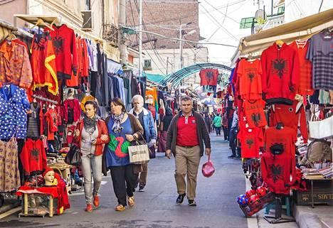 Kaupungin laajin ulkobasaari levittäytyy kilometrin mittaisena Shyqyri Bërxolli- ja Çamëria-kaduille. Patrioottisuus näkyy, ja hinnat ovat Euroopan halvimpia.