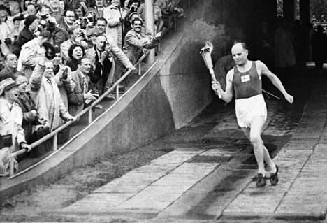 Suomalainen juoksija Paavo Nurmi tuomassa olympiatulta Olympiastadionin maratonportista Helsingin olympialaisten avajaisissa 19. heinäkuuta 1952.