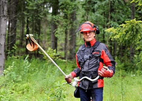 Perheen pääelinkeino on metsätalous. Tuomas Hoikkala hoitaa raivaussahalla metsää.