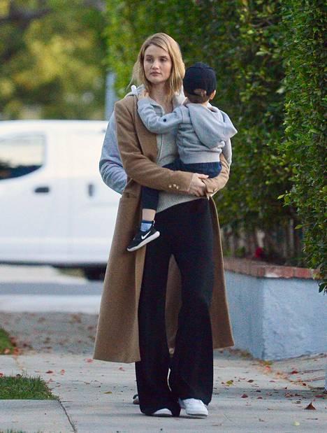 Huppari, leveälahkeiset rennot housut ja beige villakangastakki ovat sekä mukava että trendikäs yhdistelmä. Kuvassa malli Rosie Huntington-Whiteley.