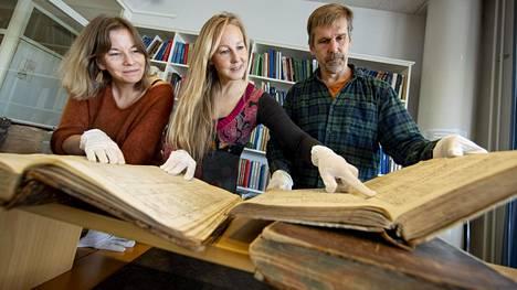 Turun yliopiston akatemianprofessori Virpi Lummaa (kesk.) sekä tutkijaryhmään kuuluvat Jenny Pettay (vas.) ja Robert Lynch kuvattuna Karjala-tietokantaan kuuluvien kirkonkirjojen kanssa.