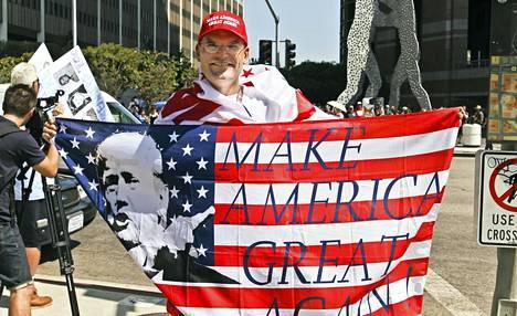 Trumpin kannattaja Arthur Schaper oli käärinyt itsensä Trump-lippuun ja päässä oli Make America Great Again -lippis.