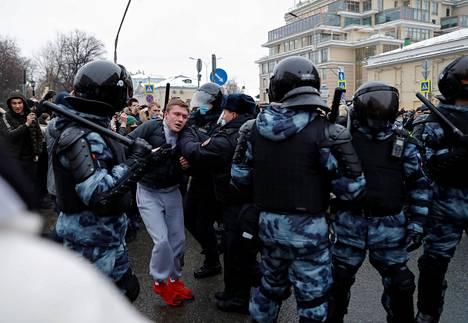 Poliisit ovat ottaneet kiinni mielenosoittajan.
