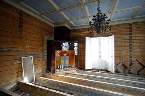 Kartanon lattiat on revitty auki ja rakennus on notkahtanut viistoon. Huoneesta toiseen kuljetaan lankunpätkien päällä.
