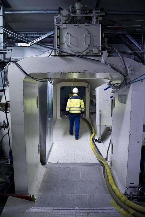 Reaktorihuoneeseen kävellään paineovien ja käytävän läpi. Oikealle ja vasemmalle jäävät reaktorin kaksi ulkoseinää.