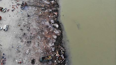 Koronavirukseen menehtyneiden ihmisten hautajaisten jälkiä ilmakuvassa Gangesin rannalla Uttar Pradeshin puolella.
