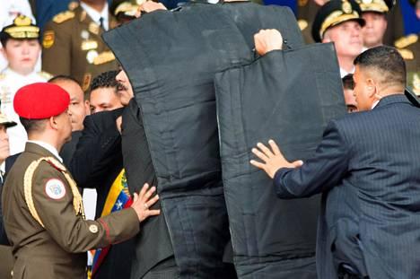 Maduron turvamiehet syöksyivät suojaamaan presidenttiä, ja tämä kuljetettiin suojattuna pois tapahtumasta.