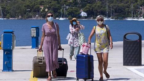 Turistit käyttivät kasvomaskeja Porosin saarella perjantaina. Saarella määrättiin maskipakko torstaina.