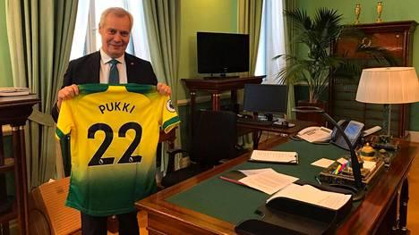 Pääministeri Antti Rinne esittelee Teemu Pukin Norwich Cityn pelipaitaa.