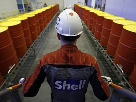 Shellin työntekijä seisoo öljytynnyreiden edessä Toržokin-tehtaalla Venäjällä.