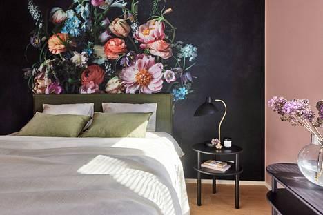 Upean valokuvatapetin värisävyt toistuvat vuodetekstiileissä ja muilla seinillä.