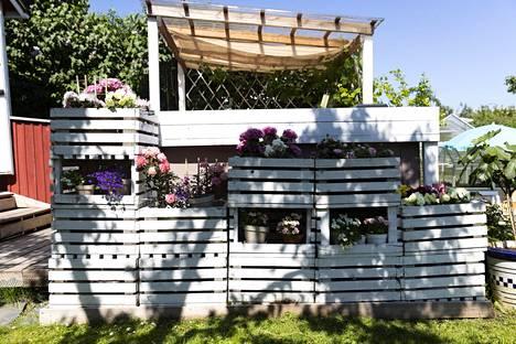 """Perheen """"ruokailuhuone"""" on ulkoterassilla. Muovikatos on peitetty tyylikkäällä juuttikankaalla, joka estää liiallisen lämmön katon kautta."""