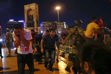 Ihmiset pakenevat Istanbulin Taksimin aukiolta. Armeijan joukot hajoittivat väkijoukkoa ampumalla ilmaan laukauksia.