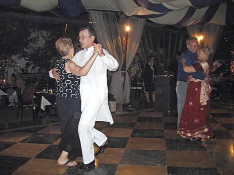 Risto Tillman tanssii valkoisissaan Kirsti Partasen kanssa ja punaiseen intialaisasuun pukeutunut Ulla Tillman Taisto Partasen kanssa Bagan illassa.