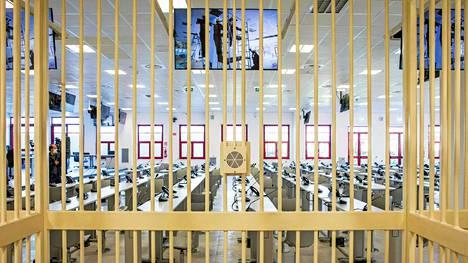 Syytetyt seuraavat oikeudenkäyntiä kaltereiden takaa salin laidalta.