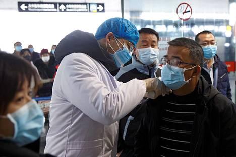 Terveysviranomainen mittasi maanantaina matkustajan kuumetta Kiinassa Changshan lentokentällä.
