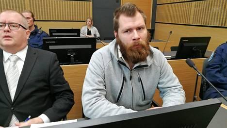 Tuomittu istui oikeudenkäynnin aluksi levollisena oikeussalissa. Oikeudenkäynti käytiin syyskuussa 2019.