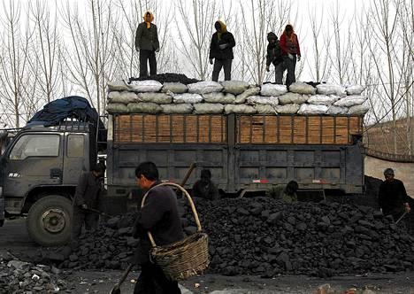 Työntekijä lataavat kuorma-auton täyteen hiiltä Dangchengin kaupungissa lähellä Pekingiä.