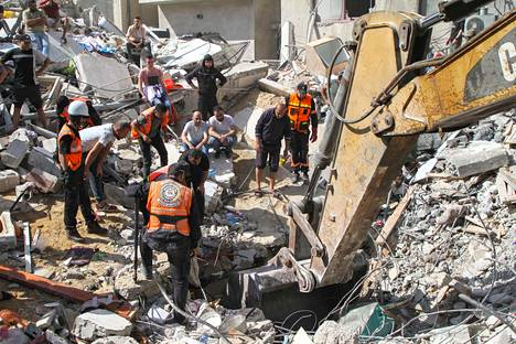 Palestiinalaiset etsivät sunnuntain tuhoisan pommi-iskun jälkeen ihmisiä sortuneiden talojen raunioista.