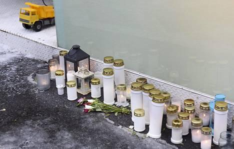 Muistokynttilöitä ja -kukkia sekä lelukuorma-auto kerrostalon edustalla Arabianrannassa Helsingissä, jossa alakouluikäinen poika surmattiin jouluaattoiltana.