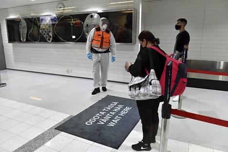 Suojavarusteisiin pukeutunut rajavartija oli vastassa Suomeen Pohjois-Makedonian Skopjesta saapuvia matkustajia tiistai-iltana Turun lentoasemalla.