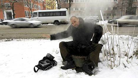 Mies lämmitteli viemäriputken päällä Bukarestissa Romaniassa torstaina.