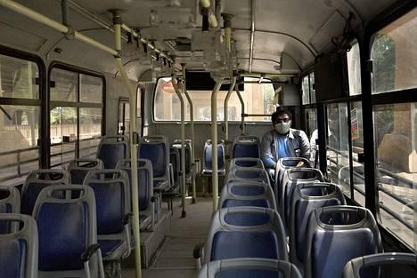 Bussin konduktööri istuu tyhjässä bussissa New Delhissä keskiviikkona, kansallisen ulkonaliikkumiskiellon ensimmäisenä päivänä.