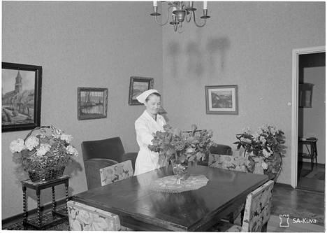 Suomen Marsalkan taloudenhoitaja neiti Aili Pohjalainen järjestelee ylipäällikön sodanaikaisessa yksityisasunnossa kukkia, joita Suomen marsalkka on saanut 75v. syntymäpäivänään.