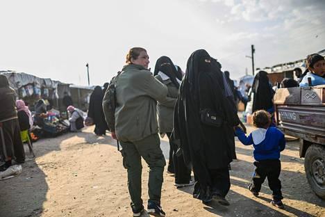 Kurdijohtoisiin SDF-joukkoihin kuuluva naissotilas saattoi al-Holin leirillä naista, jonka kerrottiin olevan Isis-taistelijan vaimo.