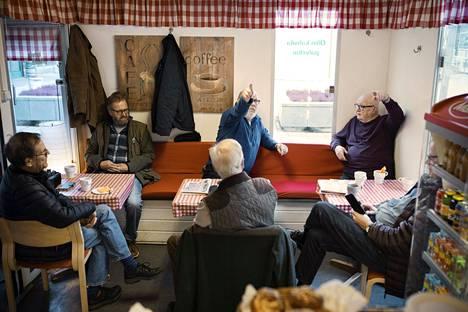 Kahvi-Ollin omistaja Olli Juvonen (oik.) keskustelemassa Timo S. Vaskelaisen (kesk.) ja muiden asiakkaiden kanssa.