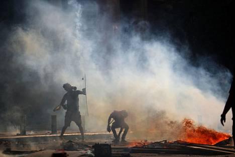 Mielenosoittaja suojasi itseään kilvellä lauantaina Beirutissa.