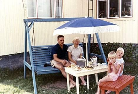 Matti-isä, Kirsti-äiti, Eija ja Pepe viettävät kahvihetkeä kotipihallaan Keravanjoen rannalla.