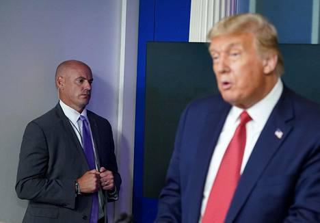 Yhdysvaltain salaisen palvelun työntekijä vartioi Trumpin takana koronatiedotustilaisuudessa.