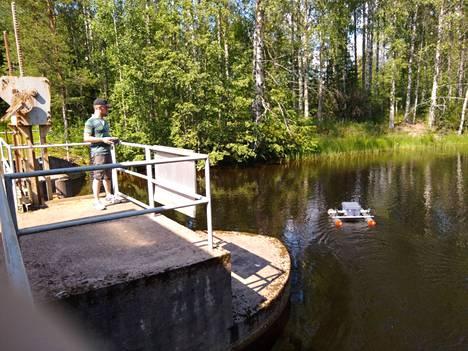 Antti ohjaa pientä venettä, jossa on viistokaikuluotain. Kuva on otettu ensimmäisellä etsintäreissulla 5. heinäkuuta.