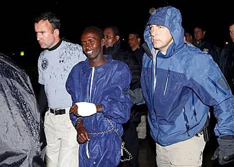 Abduhl Wali-i-Musi hymyili kameroille saapuessaan poliisien saattamana Yhdysvaltoihin.